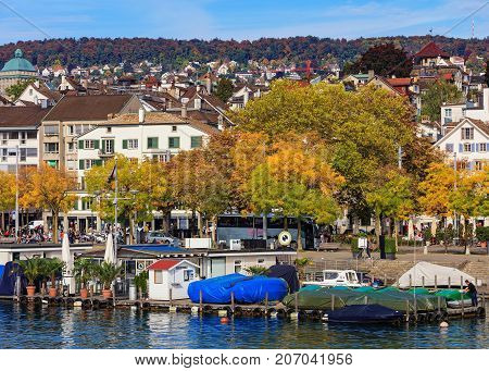 Zurich, Switzerland - 29 September, 2017: embankment of the Limmat river in the city of Zurich, old town buildings in the background. Zurich is the largest city in Switzerland and the capital of the Swiss canton of Zurich.