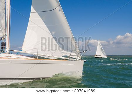 Two beautiful white yachts or sail boats sailing or racing at sea on a bright sunny day