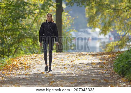 STOCKHOLM SWEDEN - OCT 01 2017: The public park Hagaparken popular for recreation walking and jogging. Woman waliking on a path in the forest. October 01 2017 in Stockholm Sweden