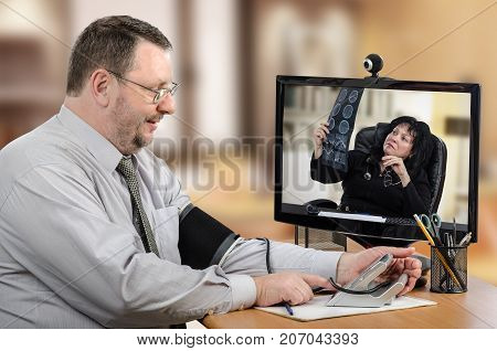 Businessman consults remote cardiologist. He measures blood pressure in front of monitor with female telemedicine doctor