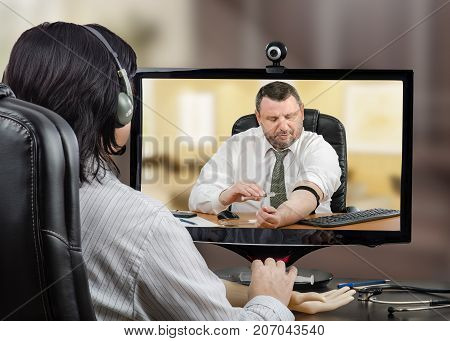 Telemedicine GP is explaining intravenous injection technique to middle aged bearded businessman during video conference