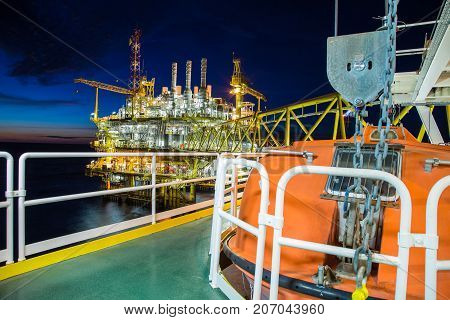 Oil and gas central processing platform and accommodation platform where life boat located for emergency use at muster station.