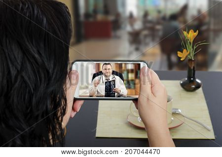 Female busy patient uses telemedicine app to talk to a doc sitting at cafe table
