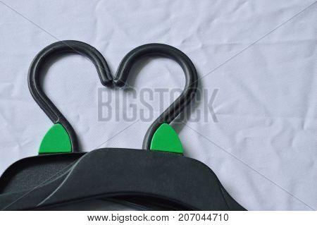 black plastic clothes hanger arranging heart shape on white fabric background