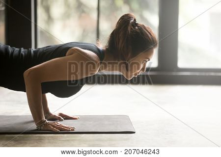 Young sporty attractive woman practicing yoga, doing Push ups, press ups, four limbed staff exercise, chaturanga dandasana pose, working out wearing black top, indoor close up image, studio background