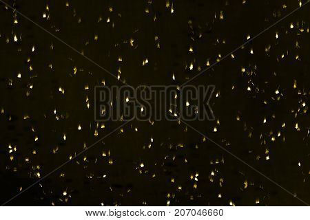 punched small metallic stars falling in front of black back