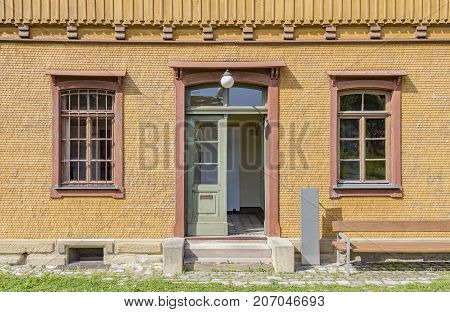 historic wood paneled house facade with barred windows in sunny ambiance