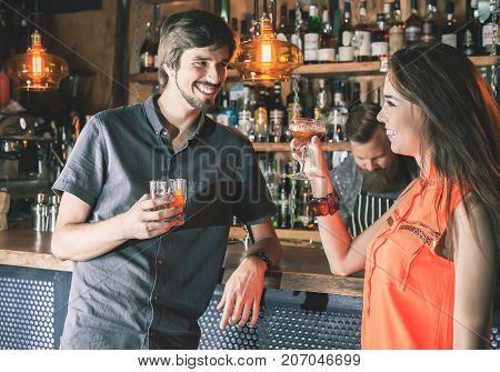 Handsome drunk man sitting at bar, drinking cocktail and looking at two attractive girls. He wants to get to know them, but does not know how. Nightclub. Date