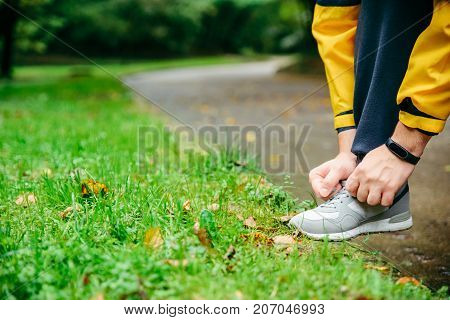 Running and sport concept.Sportsman hands tying shoelaces. autumn rainy day