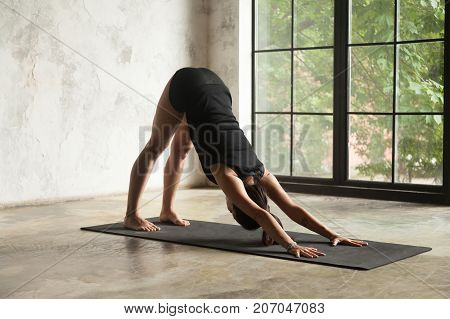 Young attractive woman practicing yoga, stretching in Downward facing dog exercise, adho mukha svanasana pose, working out, wearing black sportswear, indoor full length image, studio background