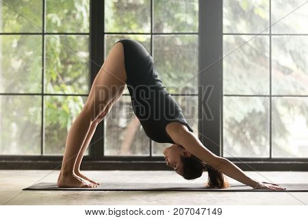 Young attractive woman practicing yoga, stretching in Downward facing dog exercise, adho mukha svanasana pose, working out, wearing sportswear, black shorts, top, indoor full length, window background