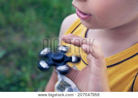 Happy smiling child playing with Spinner. Photo with depth of field.