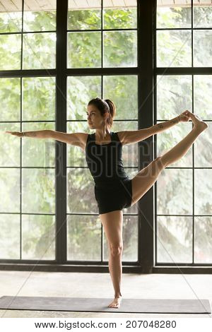 Young woman practicing yoga, standing in Utthita Hasta Padangustasana exercise, Extended Hand to Big Toe pose, working out, wearing sportswear, black shorts, top, indoor full length, studio background