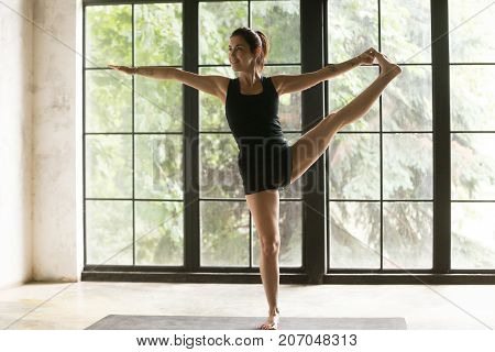 Young woman practicing yoga, standing in Utthita Hasta Padangustasana exercise, Extended Hand to Big Toe pose, working out, wearing sportswear, black shorts, top, indoor full length, house interior