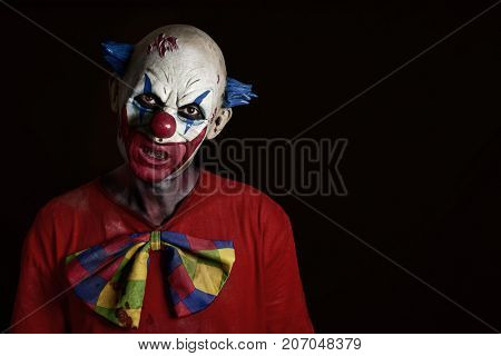closeup of a scary evil clown wearing a dirty and ragged costume with a blank black space on the right