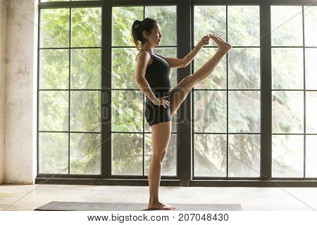 Young woman practicing yoga, standing in Utthita Hasta Padangustasana exercise, Extended Hand to Big Toe pose, working out, wearing sportswear, black shorts, top, indoor full length, window background