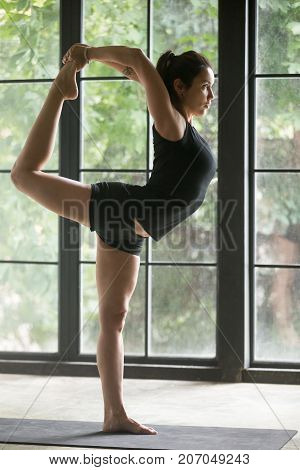Young attractive sporty woman practicing yoga, standing in Natarajasana exercise, Lord of the Dance pose, working out, wearing sportswear, black shorts and top, indoor full length, window background