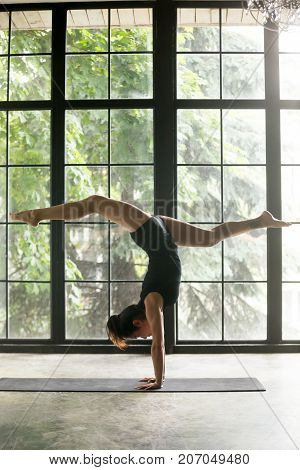 Young woman practicing yoga, standing in Adho Mukha Vrksasana exercise, handstand, Downward facing Tree pose, working out, wearing sportswear, black shorts, top, indoor full length, studio background
