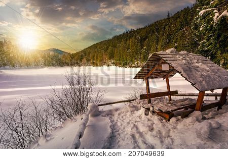 Wooden Bower In Snowy Winter Forest At Sunset