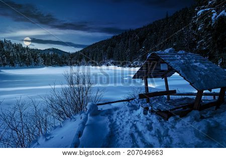 wooden bower in snowy winter spruce forest. beautiful mountainous landscape near snow covered frozen lake at night in full moon light