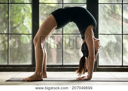 Young attractive woman practicing yoga at home, model stretching in Urdhva Dhanurasana exercise, Bridge pose, working out wearing sportswear black shorts and top, indoor full length, studio background