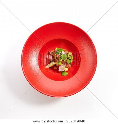 Menu in Pan-Asian cuisine - Tartar from salmon with passion fruit sauce with slices of vegetables and fresh greens on the red plate. Top view