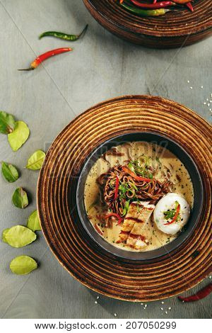 Menu of gastronomic restaurant. Soup with noodles and  coconut milk, pork and egg poached with seeds and fresh herbs in gray bowl on wooden board. Top View