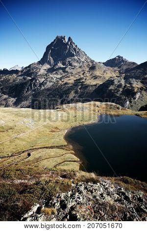 Midi Dossau Peak reflected and Gentau lake. Ossau Valley, Pyrenees National Park, Pyrenees, France.