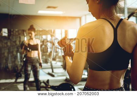 Asian Woman Lifting Dumbbell In Front Of Mirror In Fitness Gym.