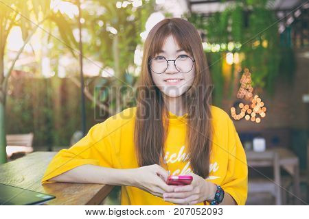 portrait cute teen waring glass slim hand hold smartphone looking at camera