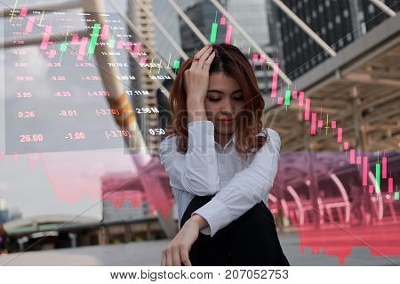 Stressed young Asian businesswoman feeling strain with trading against stock market and candlestick graphic on background. Failure economic crisis concept.