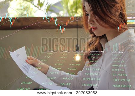 Double exposure of young attractive Asian businesswoman analyzing graphs on paperwork in office with candlestick charts background.
