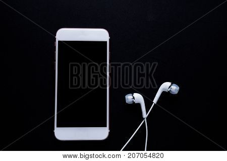 Mobile phone with earphone on dark background