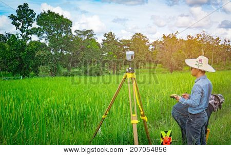 UBONRATCHATHANI THAILAND-SEPTEMBER 26 2017 : Asian smart engineer or surveyor is working on controller screen for surveying land in rice field. GPS surveying instrument.