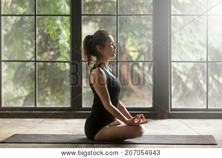 Young attractive woman practicing yoga, sitting in Padmasana exercise, Lotus pose, mudra gesture, eyes closed, working out, wearing sportswear, black shorts, top, indoor full length, window background