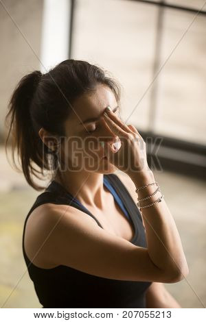 Young attractive woman practicing yoga at home, making Alternate Nostril Breathing exercise, nadi shodhana pranayama pose, working out wearing black top, wrist bracelets, indoor close up image, studio