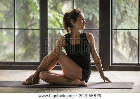 Young attractive woman practicing yoga at home, sitting in Ardha Matsyendrasana exercise, Half lord of the fishes pose, working out, wearing sportswear, black shorts, top, indoor full length, studio