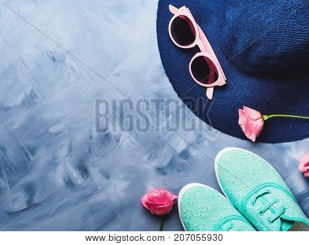 Woman's Hat, sun glasses and shoes with flowers on blue background. Fashion summer holiday accessories still life