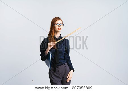 a mysterious red-haired girl with glasses is holding a ruler in her hands and pointing it aside