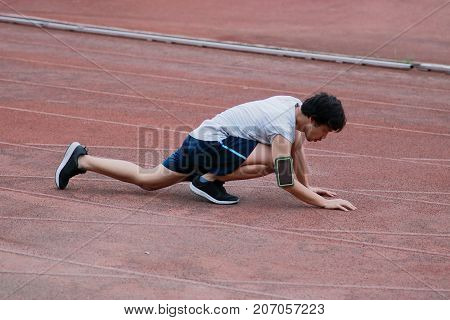 Young Asian runner injury and lying down on track during running. Accident sport concept.