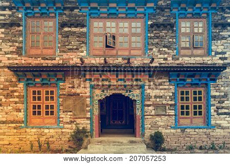 Background picture of beautiful woodcarft Nepal style windows and door in the old brick wall. Nepal travel, traditional crafting. Retro vintage toning effect