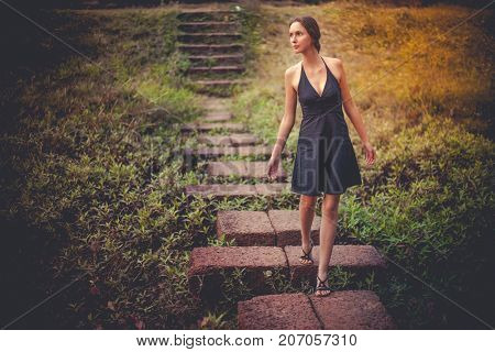Happy beautiful young woman in black dress walking down the stairs in the park, looking aside. romantic mood. Natural light, vintage toned grunge effect. Summer nature scene. Art concept