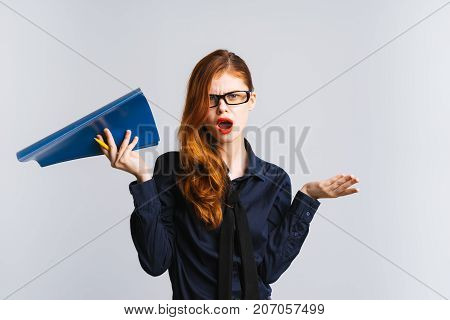 indignant red-haired girl with glasses is holding a folder in her hands, isolated