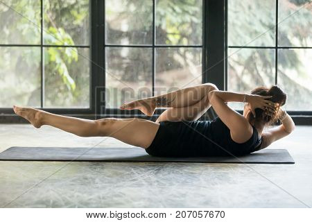 Young attractive sporty woman practicing fitness, warming up, doing crisscross bicycle crunches exercise, working out wearing black sportswear, indoor full length, studio or home background, rear view