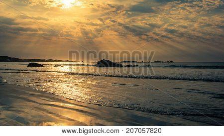 Sunburst at dusk over the beach, lights up the rocks and sand