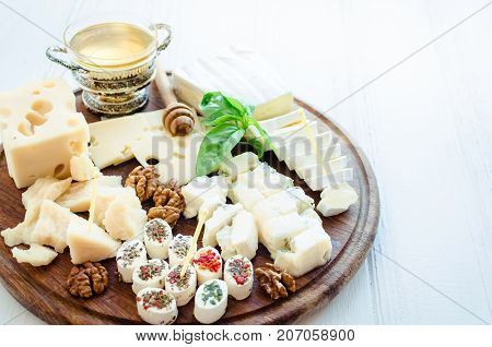 Cheese platter: Parmesan cheddar gouda gorgonzola brie and other with walnuts and honey on wooden board on white background. Tasty appetizers with different kind of cheese.