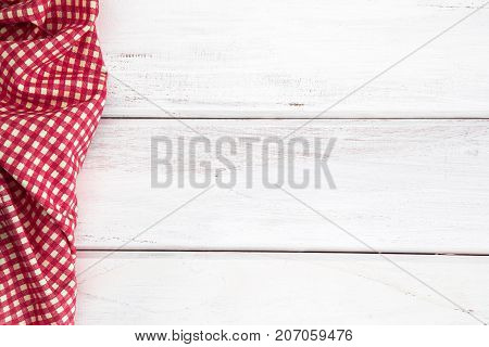 The Crumpled red checkered tablecloth or napkin on empty white wooden table with copy space for food cooking menu background concept top view or overhead shot