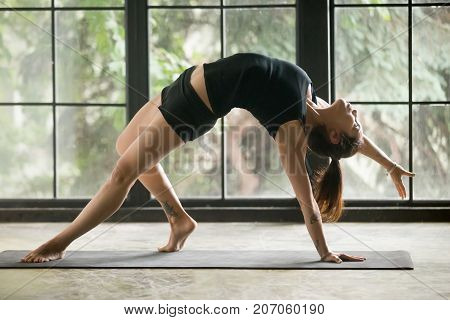 Young attractive woman practicing yoga at home, stretching in Camatkarasana exercise, Wild Thing, Flip-the-Dog pose, working out, wearing sportswear, black shorts, top, full length, studio background
