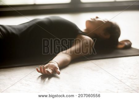 Young sporty woman practicing yoga at home, lying in Savasana exercise, Corpse pose, working out, wearing black sportswear, indoor closeup, studio floor background. Wellness concept
