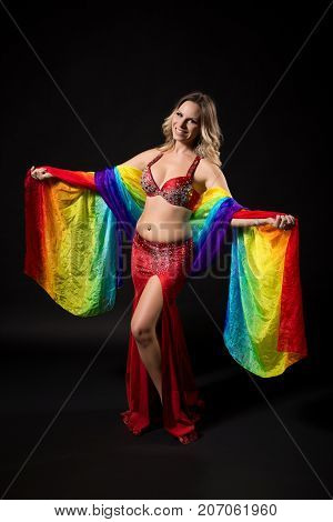 Beautiful belly dancer holding veil and performing belly dance on black background.